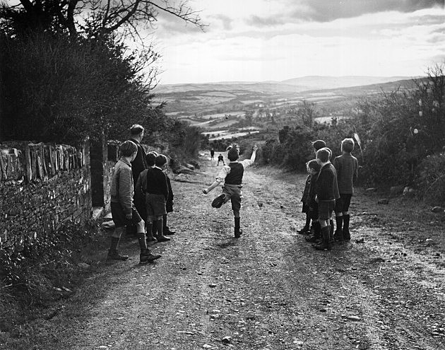 Young boys enjoy a game of road bowling in an Irish country lane.