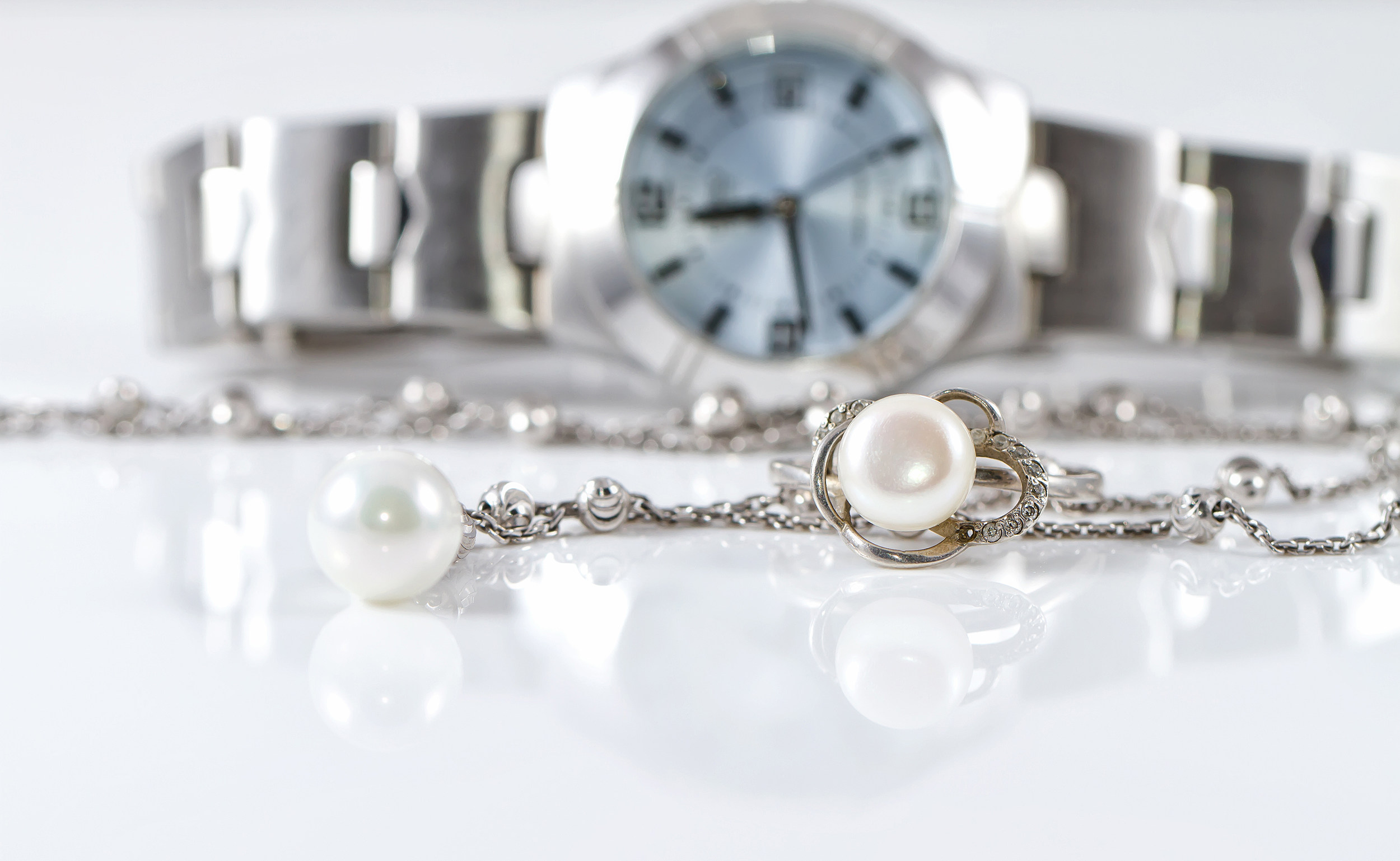 Silver ring and chain on the background of watches