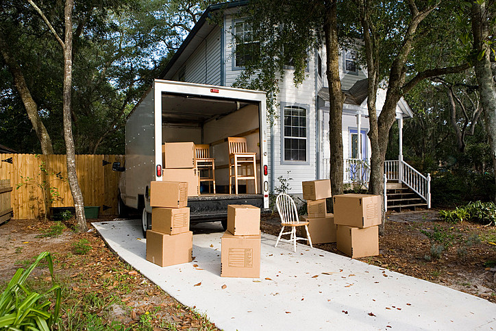 Moving van with cardboard box and chairs by house